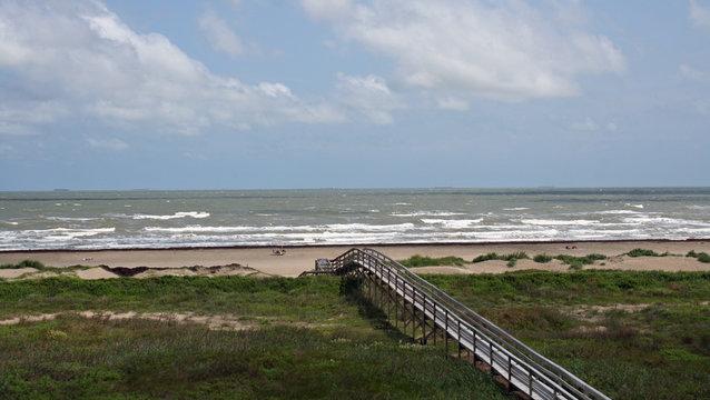 Boardwalk through green marsh grass leading to the sand and surf of Galveston Beach, Texas