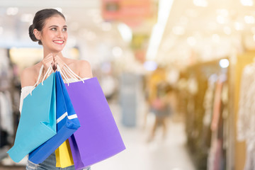 Smiling beautiful young woman holding many colorful shopping bags over Shopping malls background. happiness, consumerism, sale and people concept.