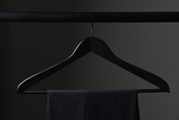 A pair of mens slacks hanging on a black hanger