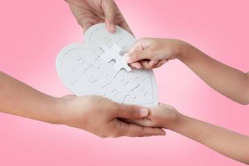 Hands of girl and mother playing jigsaw puzzle on the pink background with clipping path