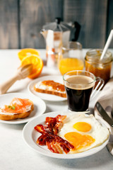 The English breakfast - eggs,  bacon,  toasts with ricotta and jam, juice in a glass, coffee on a grey background. Selective focus.