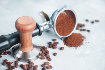 Coffee making equipment with copy space. Barista tools concept. Portafilter with ground coffee on a white background.
