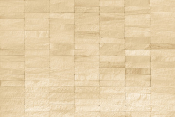 Rock stone tile wall texture rough patterned background in beige creme brown color