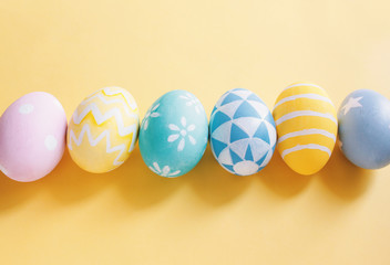 Row of pastel and colorful easter eggs with copy space on yellow background.