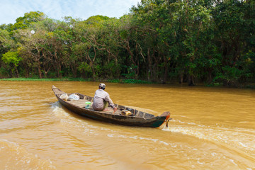 Cambodian man on small boat on river near Kompong Phluk