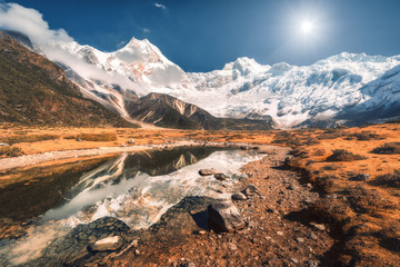 Wall Mural - Beautiful scene with high rocks with snow covered peaks, stones in mountain lake, reflection in water, blue sky in sunset. Nepal. Amazing landscape with Himalayan mountains at bright sunny day. Nature