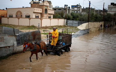 Palestinian passes a flooded street following heavy rains in Beit Hanoun town in the northern Gaza Strip