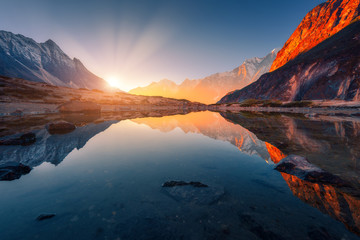 Wall Mural - Beautiful landscape with high mountains with illuminated peaks, stones in mountain lake, reflection, blue sky and yellow sunlight in sunrise. Nepal. Amazing scene with Himalayan mountains. Himalayas