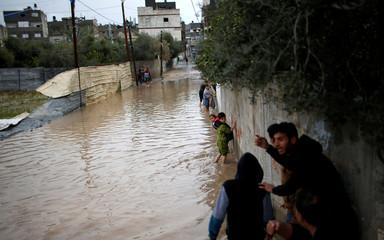 Palestinian children walk at a flooded street following heavy rains in Beit Hanoun town in the northern Gaza Strip