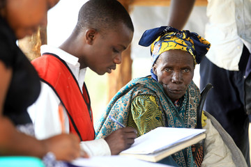 Congolese elderly woman, who migrated from Democratic Republic of Congo by fleeing on a boat across Lake Albert, waits to be registered by UNHCR in Ntoroko