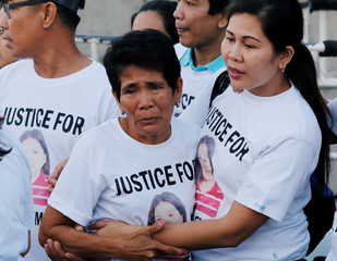 Family members wait for the arrival of the body of Joanna Demafelis, a Filipina domestic helper who was killed and found inside a freezer in Kuwait, in her hometown in Iloilo