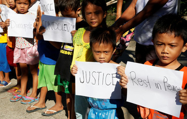 Children display placards as they wait for the convoy transporting the body of Joanna Demafelis, to pass by a Filipina domestic helper who was killed and found inside a freezer in Kuwait, in her hometown in Iloilo