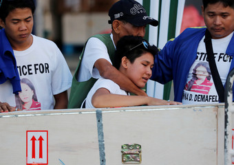 A woman cries beside a crate containing the body of her sister, Joanna Demafelis, a Filipina domestic helper who was killed and found inside a freezer in Kuwait, upon arrival in Iloilo