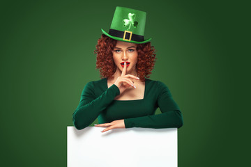 St Patrick Day. Young sexy oktoberfest woman, wearing a dress and green hat with clover, on green background with banner for copy space