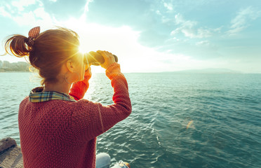 Young Girl Looking Through Binoculars At The Sea On A Bright Sunny Day, Rear View. Wanderlust Travel Journey Concept