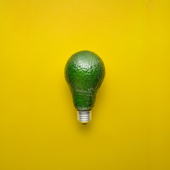 Fresh idea / Creative concept photo of avocado as electric bulb on yellow background.