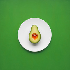 Dinner is served / Creative concept photo of avocado with heart on painted plate on green background.