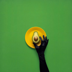 Dinner is served / Creative concept photo of avocado with hand on painted plate on green background.