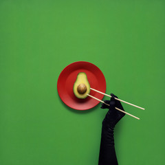 Dinner is served / Creative concept photo of avocado with hand and chopsticks on painted plate on green background.