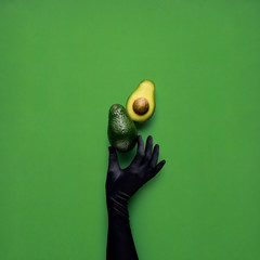 Dinner is served / Creative concept photo of avocados with hand on green background.