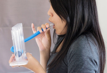 Patient using incentivespirometer or three balls for stimulate lung,Selective focus