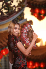 asian lady wearing traditional cheongsam dress with temple and lantern background