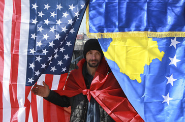 Man covered by Albanian flag walks by U.S. and Kosovo flags during celebrations of the 10th anniversary of Kosovo's independence in Pristina, Kosovo