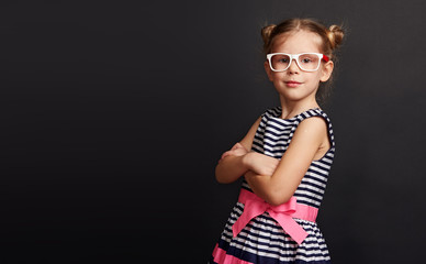 Pretty girl in spectacles standing with crossed arms over black background with copy space. Beautiful smart child at chalkboard.