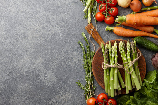 Fresh raw asparagus and other spring vegetables cooking in the kitchen, top view