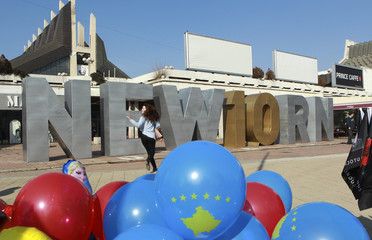"""Woman walks in front of the """"Newborn"""" monument updated for celebrations of the 10th anniversary of Kosovo's independence in Pristina"""