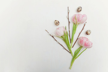 Spring greeting card. Easter eggs with pink tulips and willow branch on white wooden background. Easter concept. Flat lay. Spring flowers tulips