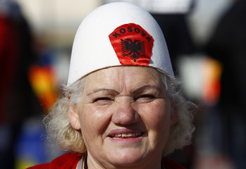 Woman in traditional hat looks on during celebrations of the 10th anniversary of Kosovo's independence in Pristina