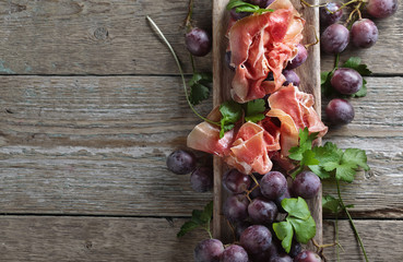 Prosciutto with parsley and grapes on a old wooden table.