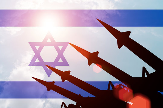 Antiaircraft rockets silhouettes on background of Israel flag. Sunny.