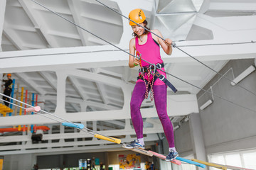 young woman in helmet and safety equipment having fun in activity rope indoor park