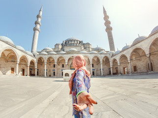 Follow me. A Muslim woman in a scarf leads her friend to the Turkish mosque Suleymaniye, travel and religion concept.