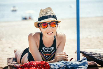 Young beautiful eastern woman on a beach sunbed