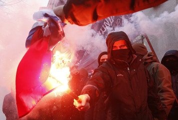 Activists and supporters of Ukrainian nationalist parties and movements burn the Russian state flag during a protest in Kiev