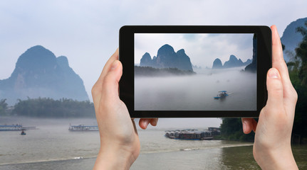 tourist photographs boat in mist on river in China