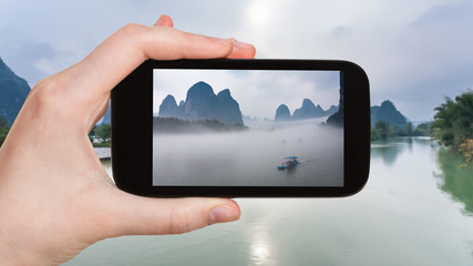 tourist photographs ships in fog on river in China