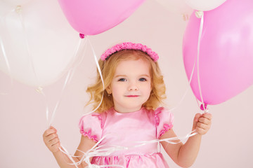 Happy cute little girl  with pink balloon heart on a pink background. mother's day, birthday