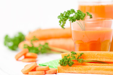 Carrot juice in beautiful glasses, cut orange vegetables and green parsley on white wooden background. Fresh orange drink. Close up photography. Selective focus. Horizontal banner