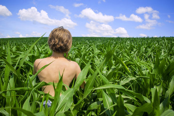 Topless girl on green corn field
