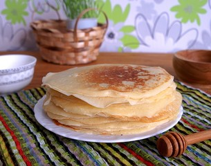 Thin pancakes with sour cream and honey