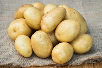 Fresh Organic Potatoes. Young Yellow Potatoes On Sackcloth With Texture Close Up.