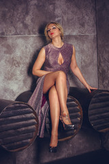 Elegantly Beautiful Woman sitting with long legs. Young and beautiful fashion model naturel over vintage background