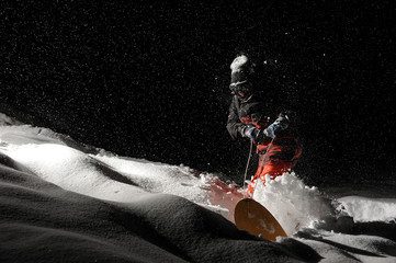 Snowboarder dressed in the orange sportswear riding with the snowboard