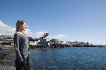 Young, blonde  Caucasian woman taking a selfie or a photograph of the Los Abrigos village in Tenerife, Canary Islands, Spain