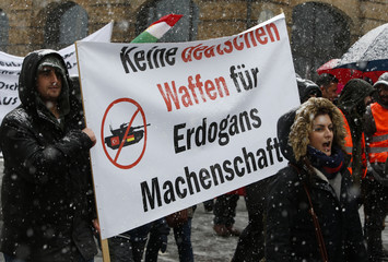 """Protesters carry a banner reading """"No German weapons for Erdogan's machinations"""" at a demonstration during the Munich Security Conference in Munich"""
