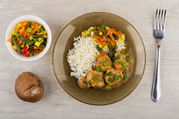 Meatballs with sauce, rice, vegetables in plate, rye bun
